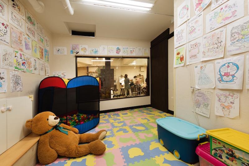 個店では珍しいほど広く、遊具やDVDも充実のキッズスペース。ガラスの向こうにママの姿が見えると、子どもは安心して遊んでくれるという。パパが一緒に来店して遊ぶファミリーも