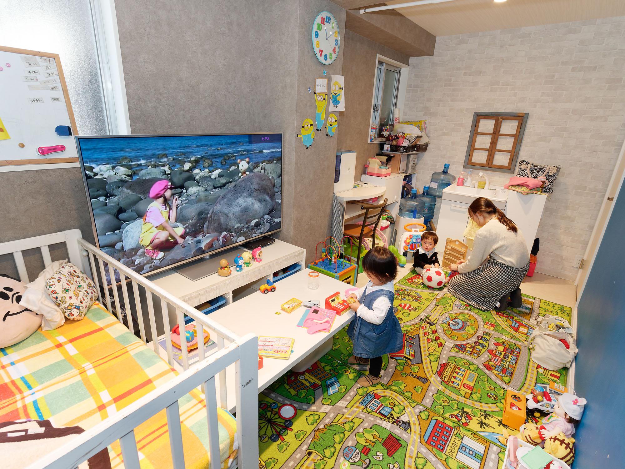 おもちゃがいっぱいのキッズスペース。右側の壁は子どもたちが自由に絵を描ける黒板になっている